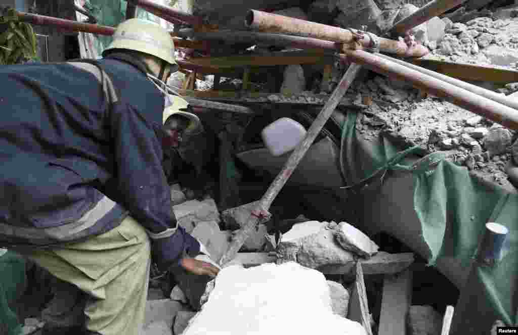 Rescuers search for survivors amongst the rubble of a collapsed building in the Kariakoo district of central Dar es Salaam, Tanzania, March 29, 2013.