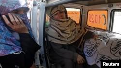 一名遇难者的母亲12月18日在卡拉奇的一家医院外在女儿遗体旁哭泣