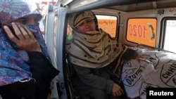 Rukhsana Bibi cries while sitting next to the body of her daughter Madiha, a worker of an anti-polio drive campaign, in an ambulance outside Jinnah Hospital in Karachi December 18, 2012.