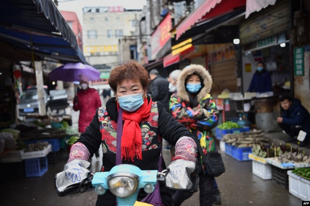 一名戴着口罩的妇女骑着电动车穿过武汉市的一个市场。(2020年1月24日)(photo:VOA)