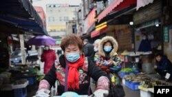 一名戴著口罩的婦女騎著電動車穿過武漢市的一個市場。 (2020年1月24日)