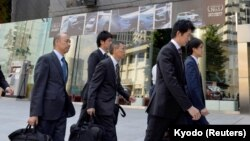 Transport ministry officials arrive at Mitsubishi Motors Corp.'s headquarters building for a raid after the company admitted to manipulating test data to overstate the fuel economy, in Tokyo, Japan, May 13, 2016.
