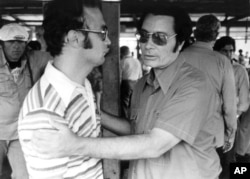 Rev. Jimmy Jones, founder of People's Temple, clasps an unidentified man at Jonestown, Nov. 18, 1978, during Congressman' Leo J. Ryan's visit.