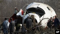 FILE - In this April 14, 2010, photo, Russian emergency ministry workers prepare to load part of the wreckage of the Polish presidential plane on a transporter outside of Smolensk airport, western Russia.