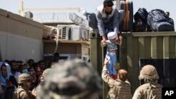美國陸軍發布的照片顯示,在喀布爾哈米德·卡爾扎伊國際機場,一名阿富汗男子把他的孩子交給英軍傘兵,美國陸軍82空降師成員在旁執行安全警戒。(2021年8月26日)