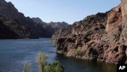 FILE - Hikers make their way along the banks of the Colorado River near Willow Beach, Ariz.