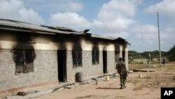 Seorang anggota pasukan keamanan Kenya berjalan melewati pos polisi di pemukiman Kamuthe di wilayah Garissa, Kenya, yang rusak akibat serangan para ekstremis al-Shabab, Senin, 13 Januari 2020.