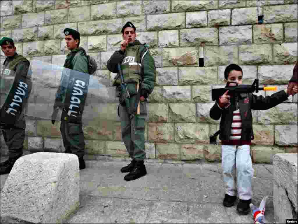 فلسطین میں ایک بچہ پولیس اہلکاروں کی طرح پستول لئے ہوئے ہے۔