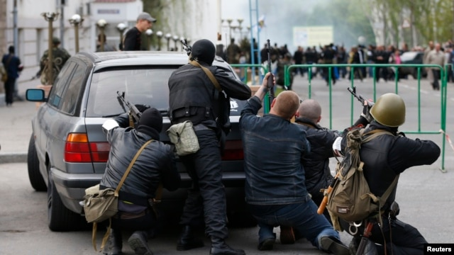 Pro-Russian armed men take cover behind a car near the local police headquarters in Luhansk, eastern Ukraine, April 29, 2014.