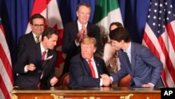 Presiden Donald Trump (tengah) bersalaman dengan Perdana Menteri Kanada Justin Trudeau disaksikan Presiden Meksiko Enrique Pena Nieto usai menandatangani kesepakatan perdagangan baru antara AS, Kanada, dan Meksiko, di Buenos Aires, Argentina, 30 November 2018.