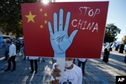 FILE - A protester from the Uighur community living in Turkey holds an anti-China placard during a protest in Istanbul, Oct. 1, 2020, against what they allege is Chinese oppression of Muslim Uighurs in far-western Xinjiang province.
