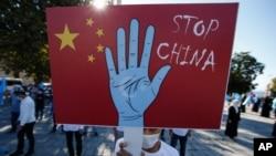 Seorang pengunjuk rasa dari komunitas Uighur yang tinggal di Turki, memegang plakat anti-China saat melakukan protes, 1 Oktober 2020. (Foto: AP)