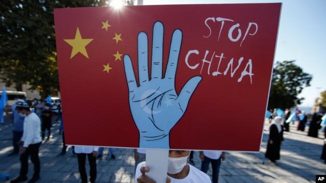 一名居住在土耳其的维吾尔抗议者在伊斯坦布尔举行的抗议活动中举着标语牌,抗议他们所称的中国政府对新疆穆斯林维吾尔人的迫害。(2020年10月1日)