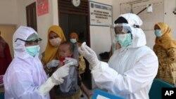 Trabajadores de salud preparan una vacuna contra el sarampión para aplicarla a un niño en Indonesia. [Foto de archivo]