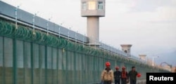FILE - Workers walk by the perimeter fence of what is officially known as a vocational skills education center in Dabancheng in Xinjiang Uighur Autonomous Region, China, Sept. 4, 2018.