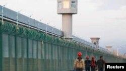 Radnici hodaju pored zaštitne ograde zdanja koje je zvanično poznato kao centar za razvoj profesionalnih vještina u Dabančengu u Ksinjiang ujgurskoj autonomnoj oblasti, Kina, 4. septembra 2018.