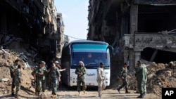 FILE - In this photo released on April 30, 2018 by the Syrian official news agency SANA, Syrian government forces gather in front of a bus carrying al-Qaida-linked fighters during an evacuation from the Palestinian refugee camp 0f Yarmouk, near Damascus,
