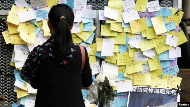 A girl stands in front of flowers and notes left by mourners for those who died in a ferry collision on Monday at a ferry pier during a three-day, city-wide mourning period in Hong Kong, October 4, 2012.