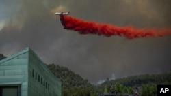 Un avión lanza retardante sobre casas en el área de Basalt, Colorado, el miércoles, 4 de julio de 2018, durante un incendio en Lake Christine.