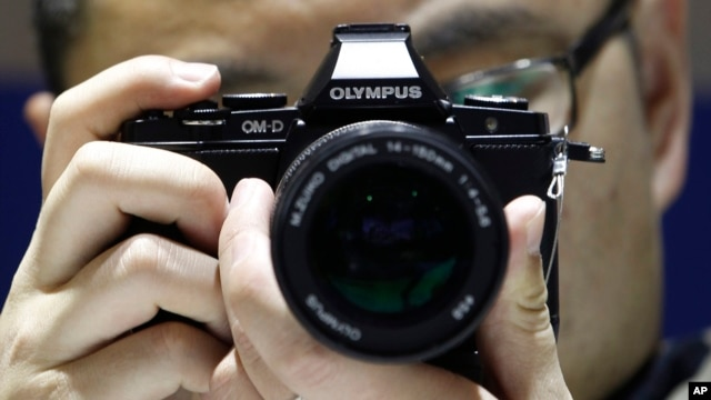 A Chinese visitor tries an Olympus digital camera during the China Photograph and Electrical Imaging Fair in Beijing, April. 20, 2012.