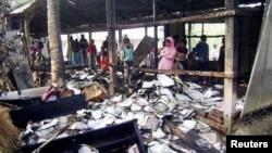 Жители городка Фени смотрят на сгоревшие учебники в школе, где должен был открыться избирательный участок. Почти 60 избирательных участок были сожжены в Бангладеш. 4 января 2014 г.