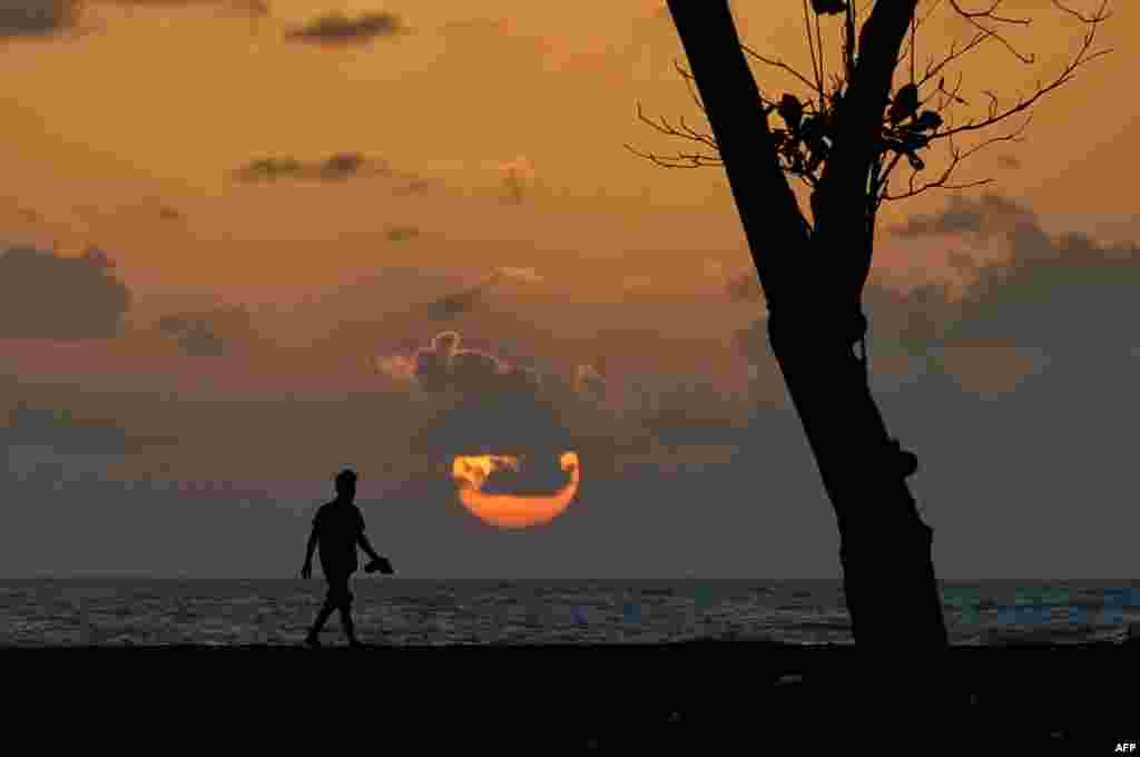 បុរសម្នាក់រស់នៅខេត្តអាចេ (Aceh) កំពុងមើលថ្ងៃលិចនៅឆ្នេរសមុទ្រMeulaboh ក្នុងខេត្តអាចេ ប្រទេសឥណ្ឌូនេស៊ី។