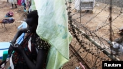 A displaced South Sudanese woman makes a cell phone call at a barbed wire fence in the UNMISS Tongping camp in Juba on February 19, 2014. Thousands are still in the camps, too afraid to go home.