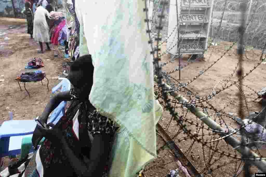 Uma mulher sul-sudanesa usa o seu telefone encostada a uma cerca de arame farpado no campo para deslocados no acampamento do UNMISS em Tongping, Juba, Sudão do Sul, Fev. 19, 2014.