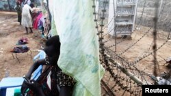A South Sudanese woman displaced by the fighting uses her phone as she leans against a barbed wire in a camp for displaced persons in the UNMISS compound in Juba, February 19, 2014.