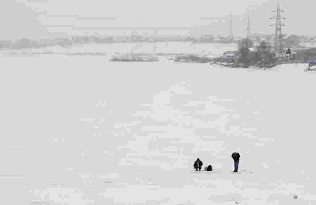 Two men fish on a frozen lake near Bucharest February 2, 2012. (Reuters)