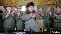 Lãnh đạo Bắc Triều Tiên Kim Jong Un vỗ tay trong cuộc giám sát hệ thống phóng tên lửa tại một địa điểm không được tiết lộ.