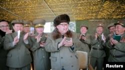 朝鲜领导人金正恩在观看新型大口径多管火箭发射装置的展示时鼓掌。(这张不具时间地点的照片由朝鲜中央通讯社发布)