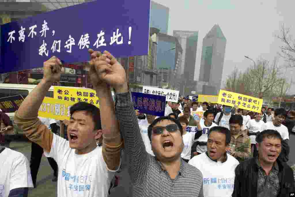 Chinese relatives of passengers onboard flight MH370 shout in protest as they march towards the Malaysian embassy in Beijing, March 25, 2014.