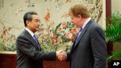 왕이 중국 외교담당 국무위원 겸 외교부장(왼쪽)과 마이런 브릴리언트 미국 상공회의소 수석부회장 겸 국제관계 대표가 19일 베이징의 외교부 청사에서 회담에 들어가기 전 악수를 나누고 있다.