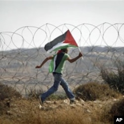 A protester carries a Palestinian flag along Israel's separation barrier near the West Bank city of Ramallah, July 9, 2011