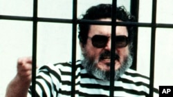 FILE - Abimael Guzman, the founder and leader of the Shining Path guerrilla movement, shouts inside of a jail cell after being captured in Lima, Peru, in this September 1992 photo.