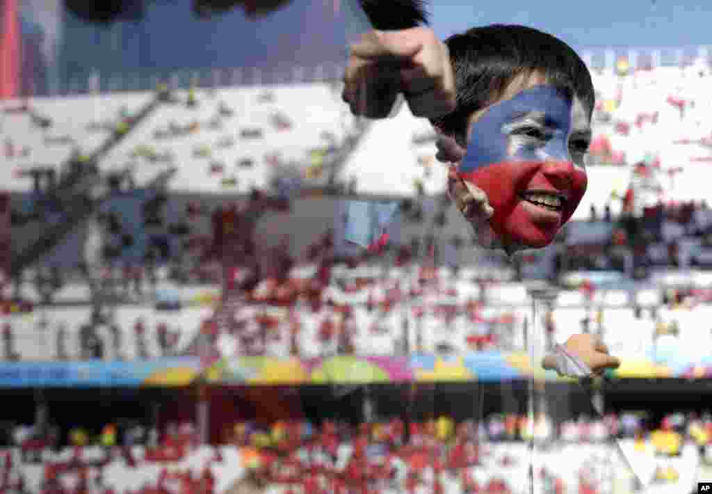 A young Chilean fan looks out onto the pitch before the group B World Cup soccer match between the Netherlands and Chile at the Itaquerao Stadium in Sao Paulo, Brazil.