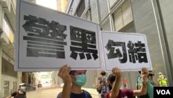 兩名年輕人7月19日下午在元朗西鐵站附近高舉抗議警方的大型標語,他們一度被警方截查。(美國之音湯惠芸)