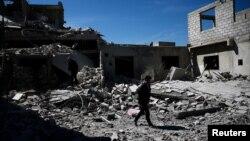 Des gens marchent près de bâtiments détruits dans le quartier de Douma, à Damas, le 4 avril 2017.