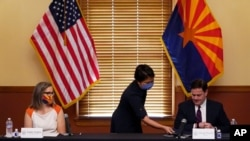 Arizona Secretary of State Katie Hobbs, left, looks on as Elections Director Bo Dul gives Gov. Doug Ducey documents to sign to certify the results for federal, statewide, and legislative offices and statewide ballot measures, Nov. 30, 2020 in Phoenix.