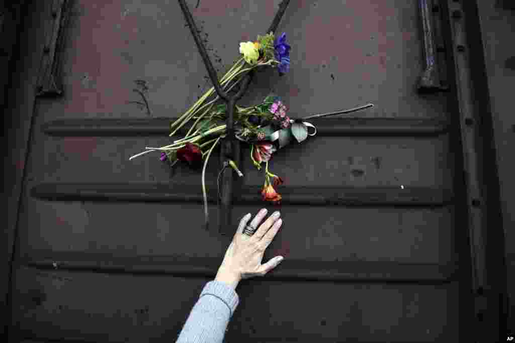 A woman places flowers on a train wagon at the old train station in Thessaloniki, Greece, to mark the 74th anniversary of the roundup and deportation of its Jews to Nazi extermination camps during World War II.