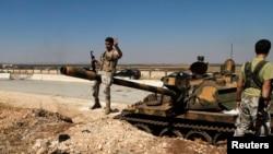 Halep'te hava üssünü ele geçirdikten sonra zafer işareti yapan isyancılar