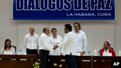 Wakil pemerintah Kolombia, Humberto de la Calle (kiri) berjabat tangan dengan Ivan Marquez, wakil dari pemberontak FARC, setelah menyepakati perjanjian ganti rugi korban perang di Havana, Kuba, Selasa (15/12).