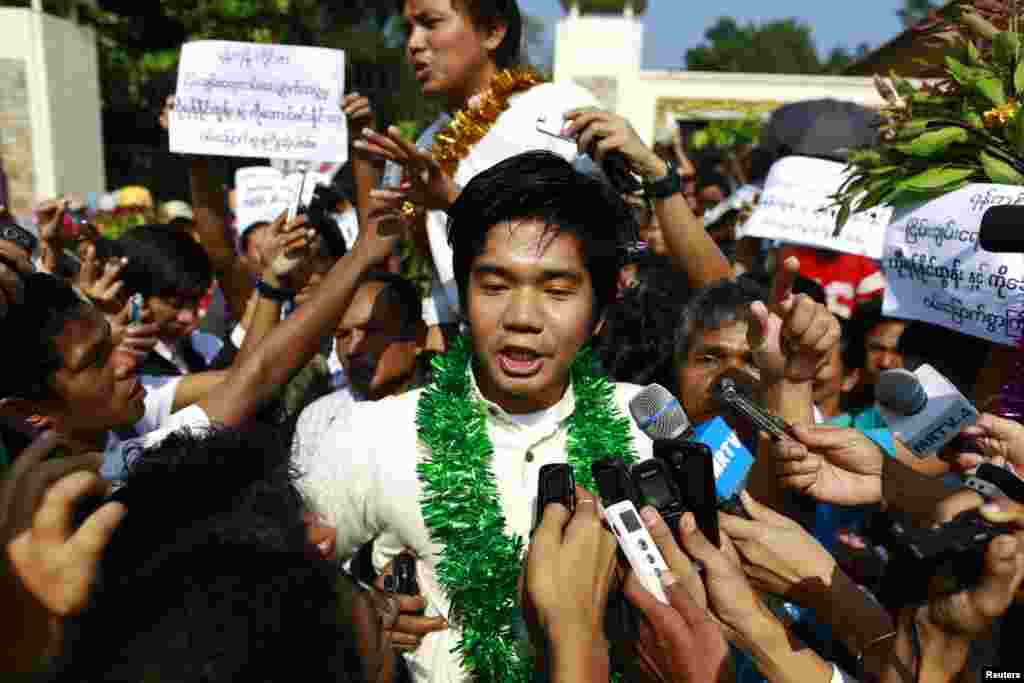 Political prisoners Yan Naing Tun (C) and Aung Min Naing (back C) talk to the media after being released from Insein prison in Rangoon, Burma, Dec. 31, 2013.