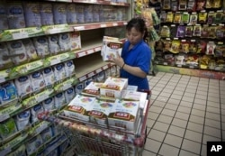 FILE - A worker removes boxes of Yili infant milk powder from a Beijing supermarket's shelves during a product safety recall in June 2012.