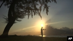 In this Wednesday, Jan. 6, 2016 file photo, a man is silhouetted against the rising sun in Singapore during his morning exercise along the eastern coast of Singapore. (AP Photo/Wong Maye-E, File)