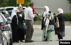 Members of a family react outside the mosque following a shooting at the Al Noor mosque in Christchurch, New Zealand, March 15, 2019.