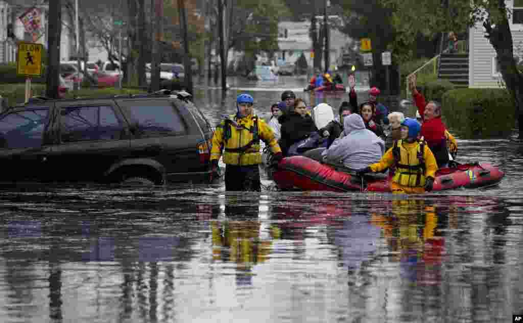 Un grupo de personas pasan la voz a aquellos que se encuentran a salvo mientras son rescatados en bote en Little Ferry, New Jersey luego que la fuerte tormenta inundara sus hogares y se quedaran sin energía eléctrica.