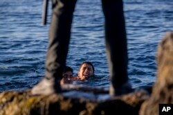 Seorang penjaga sipil Spanyol menunggu para migran di daerah kantong Spanyol Ceuta, dekat perbatasan Maroko dan Spanyol. (Foto: AP)