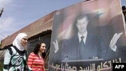 Dve gradjanke Sirije prolaze pored postera predsednika Bašara al Asada